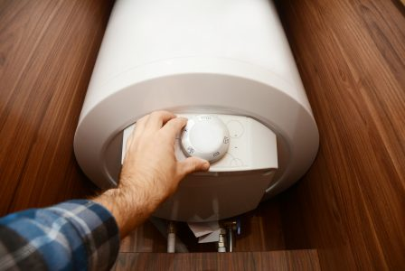 Man hand regulating heat of home boiler