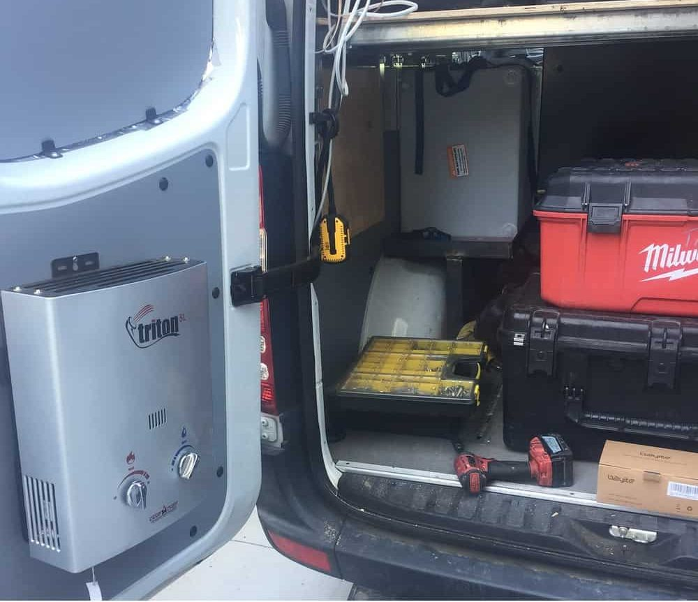 A tankless water heater installed at the back of a van