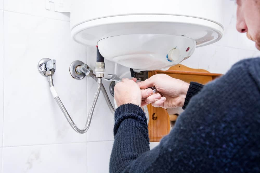 Person repairing a tankless water heater