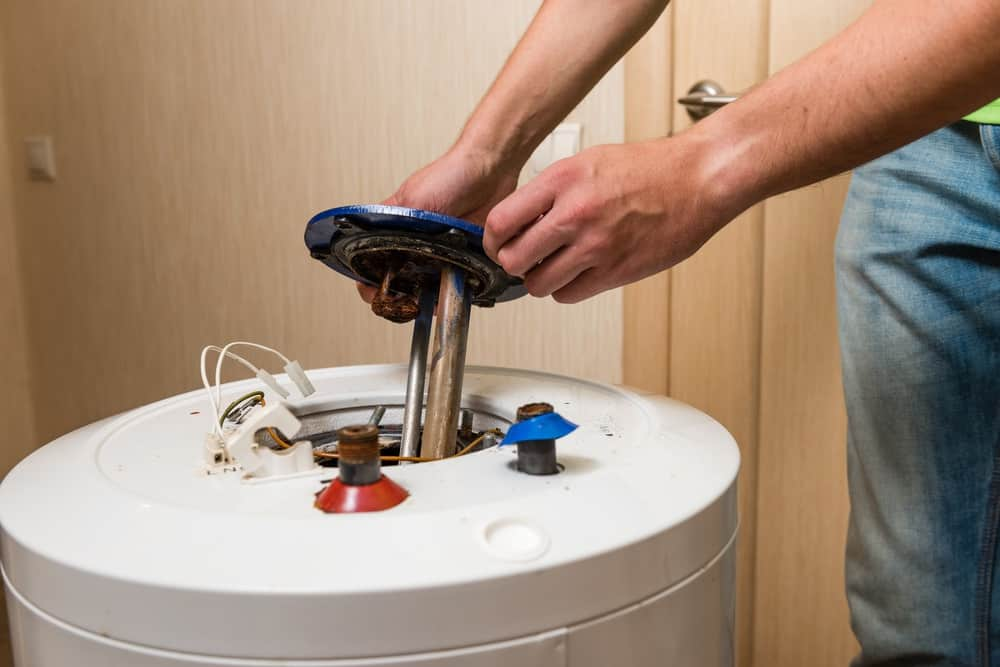 Man opening the lid of a water heater to check for problems