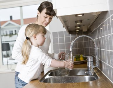 Mom helping her daughter get water from the kitchen faucet