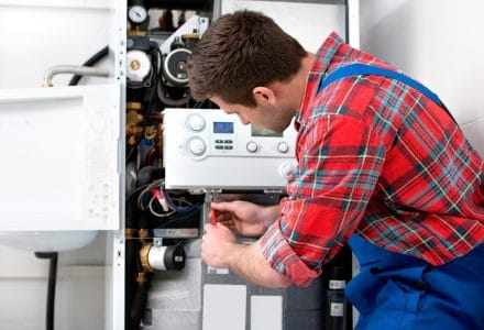 Technician troubleshooting a problem of a tankless water heater