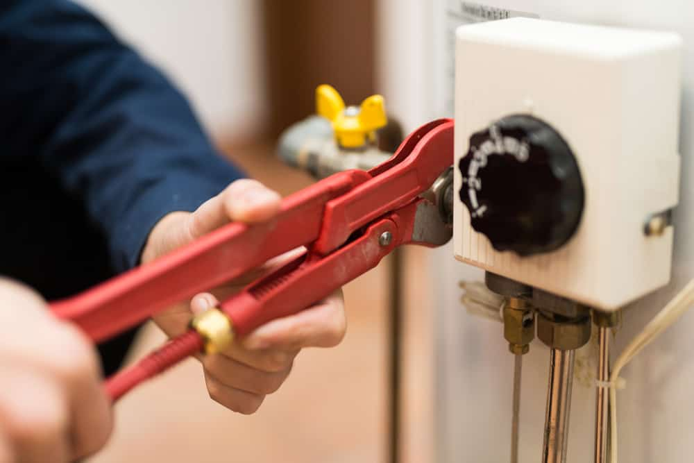 Man adjusting a fitting in the water heater panel