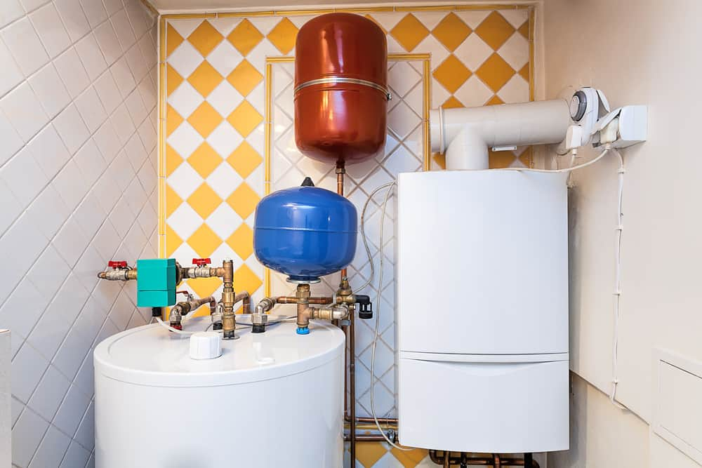Indoor heating system with tank and tankless water heater