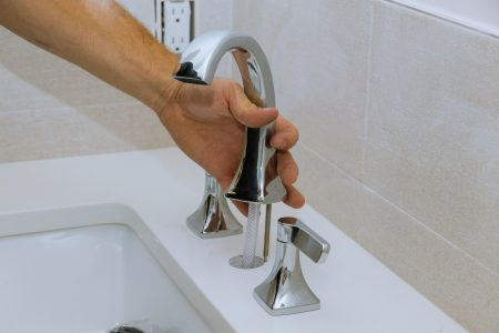 Plumber installing water faucet in the bathroom