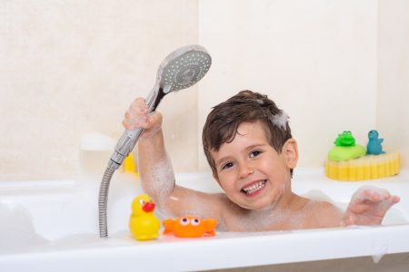Kid bathing in a tub with shower
