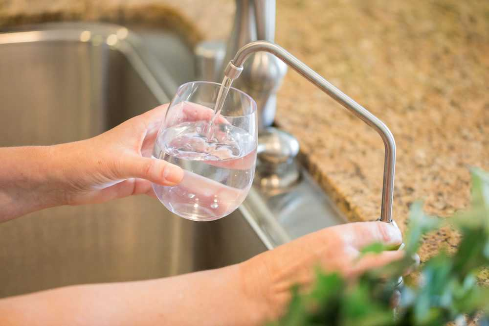 Woman getting reverse osmosis water from tap