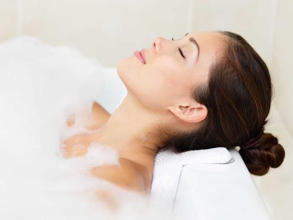 Woman in a bathtub leaning on a bath pillow