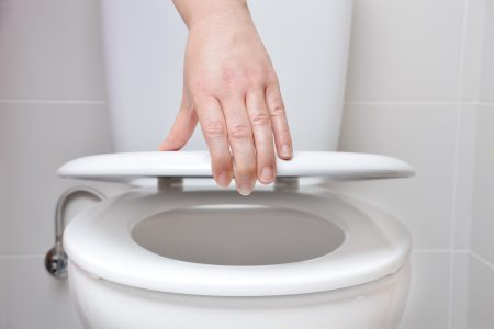 Woman closing the toilet seat