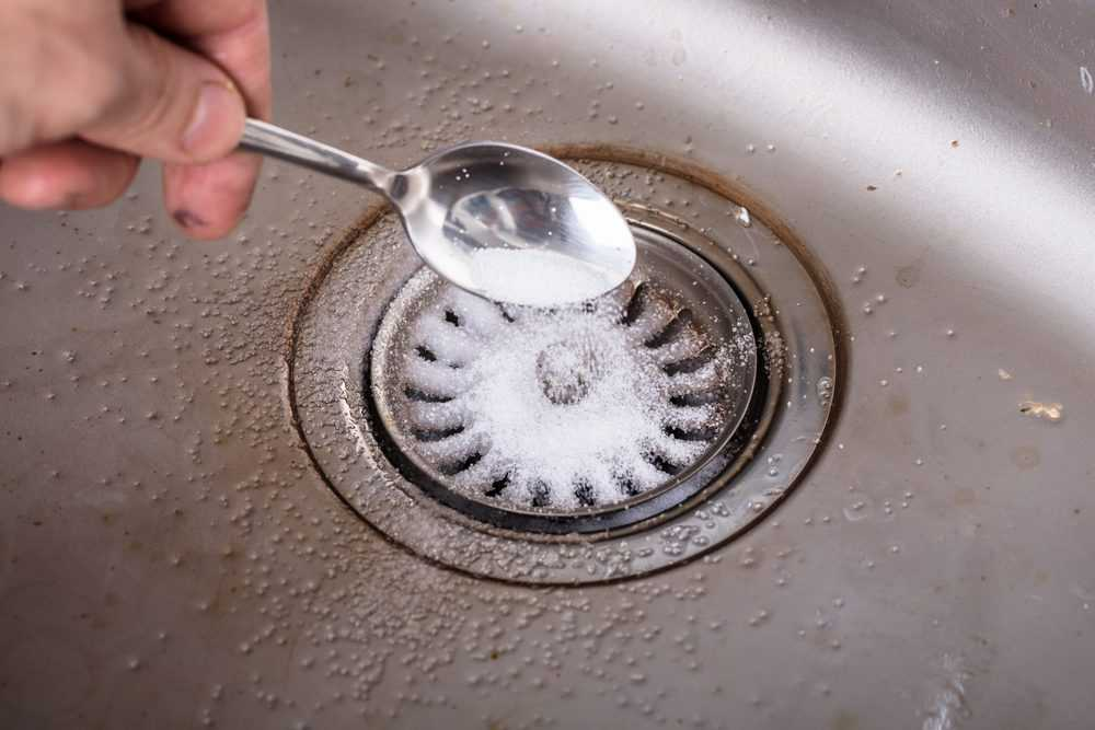 Person unclogging the sink with baking soda.