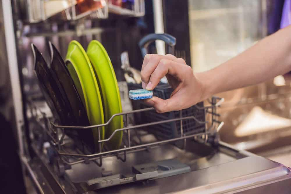 Woman putting detergent tablet in dishwasher