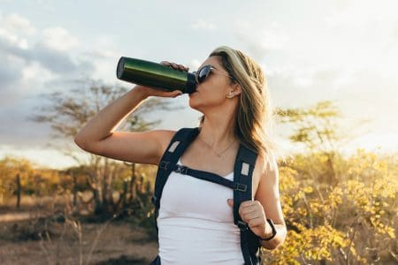 Woman drinking from a water bottle during a hike