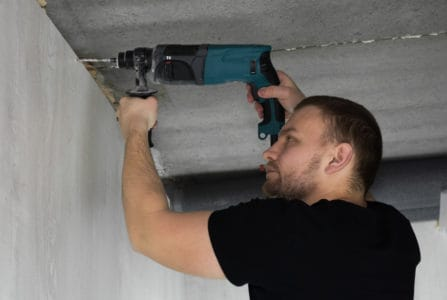 Man drilling into concrete wall with a hammer drill