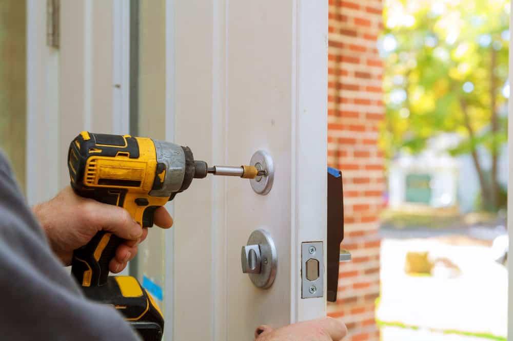 Man drilling on a door lock