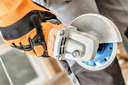 Man holding a mini circular saw