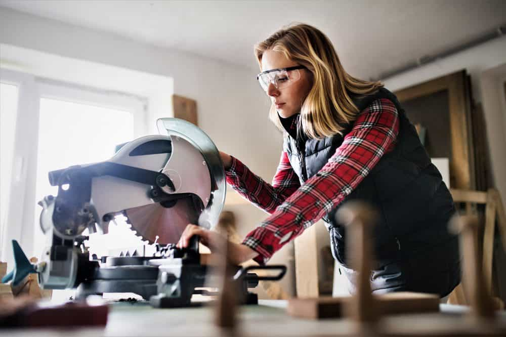 Woman operating a miter saw