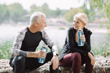 Middle aged couple drinking from smart water bottles