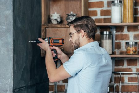 Man drilling living room wall with drill