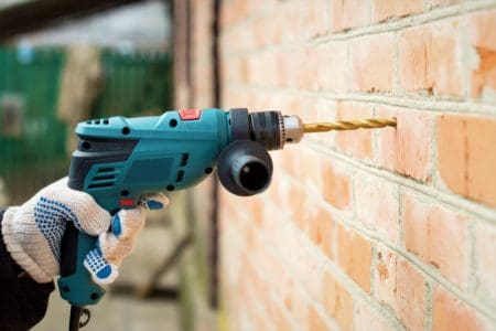 Electric drill against a brick wall