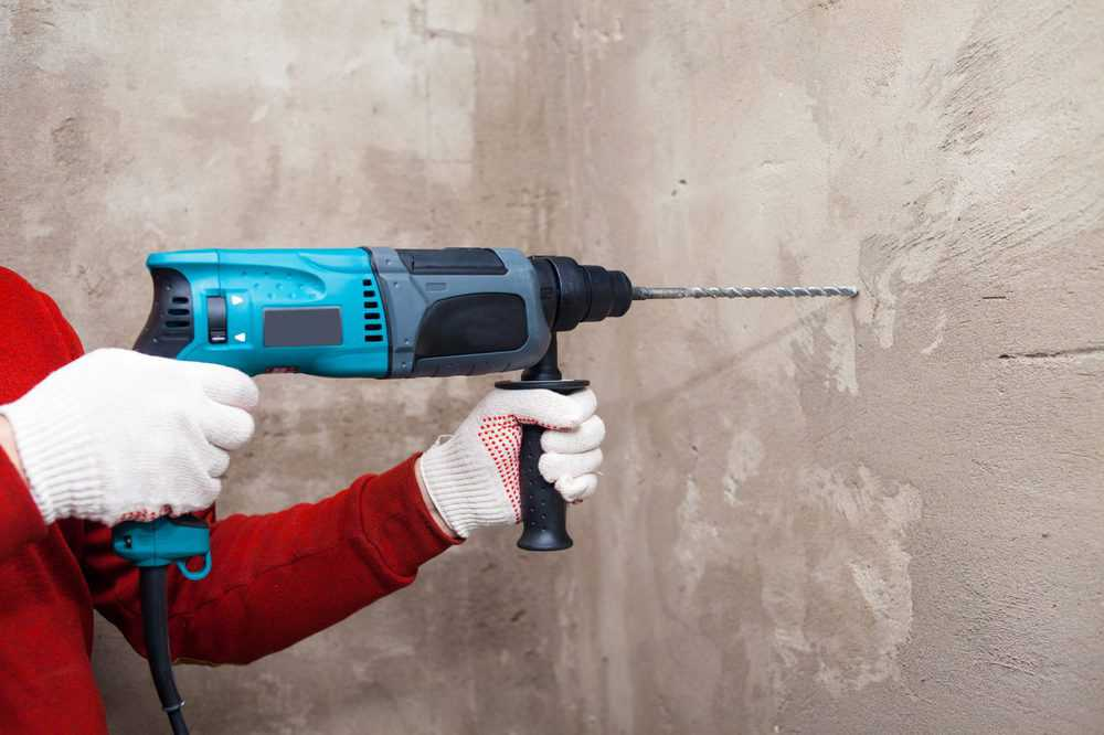 Man drilling into a concrete wall using an impact drill