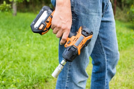 Man holding a battery powered impact wrench