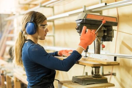 Woman working with a benchtop drill press