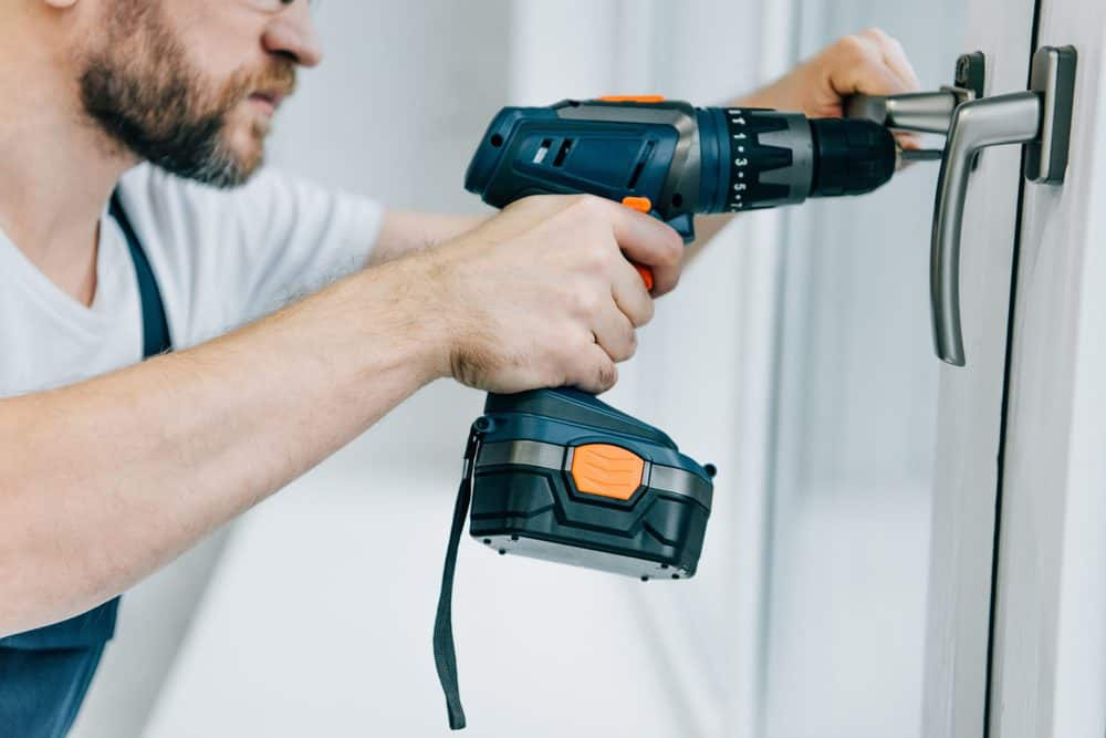Man drilling into a lock with a cordless drill