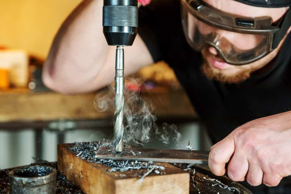 Man drilling through metal with an electric drill