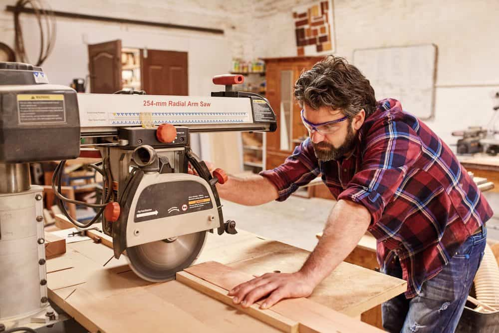 Carpenter using radial arm saw to cut wood in workshop