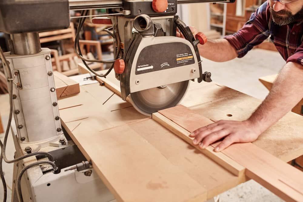 Radial arm circular saw cutting through wooden plank