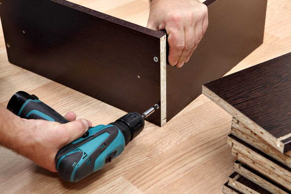 Man building a cabinet with a cordless screwdriver