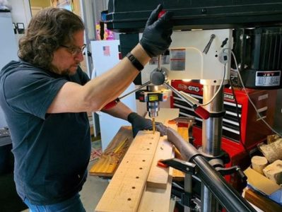 Man working with a floor drill press