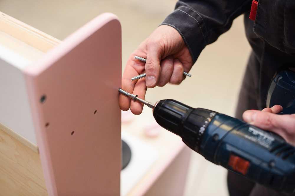 Carpenter tightening screws with screw gun