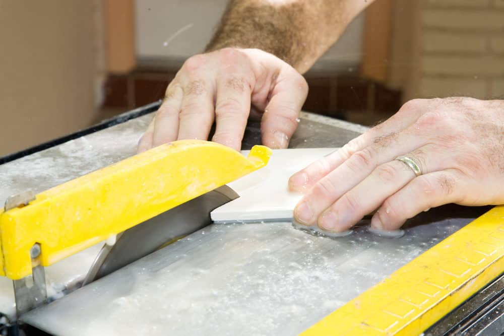 Man cutting ceramic tile with a table saw
