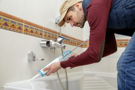 Man applying bathtub caulk