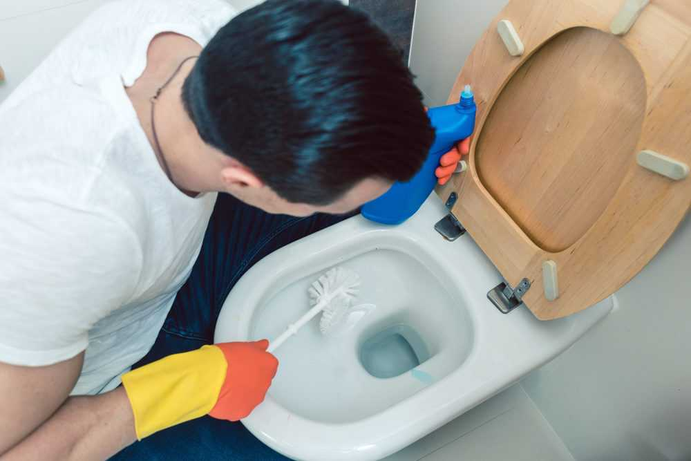 Man cleaning toilet with a toilet brush