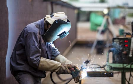 Worker with proective mask welding metal