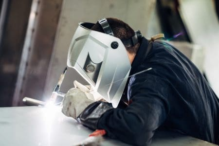 Man welding with head mask