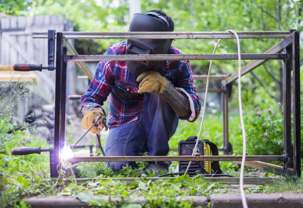 Man in a protective mask welding metal construction outside