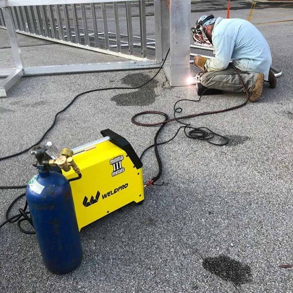 Man welding a fence with a 110 volt welder