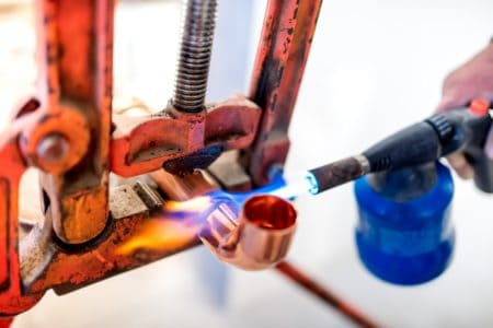 Worker using propane gas torch for soldering copper pipes.