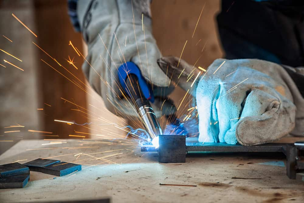 Man with welding gloves holding a gas torch