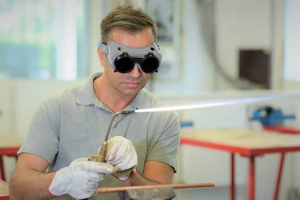 Man wearing welding goggles while using a gas torch