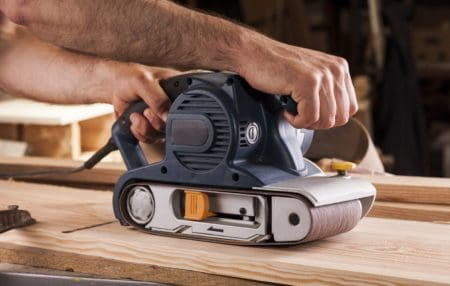 Carpenter works with belt sander for woodworking