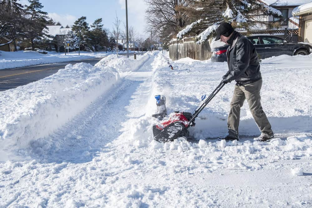 Man clearing snow with a cordless snow blower