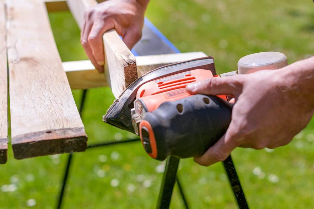 Sanding wooden stool with a detail sander
