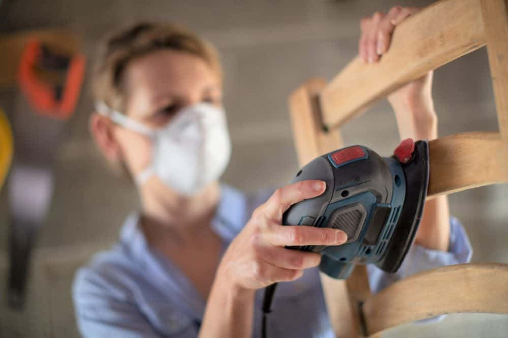 Woman sanding wooden chair with a palm sander