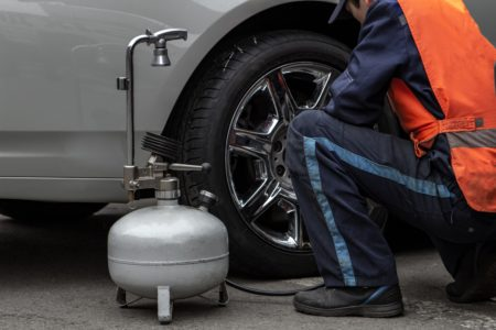 Man inflating car tire with a pancake air compressor