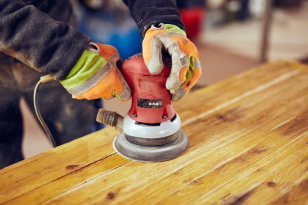 Carpenter using orbital electric sander on a retro vintage table