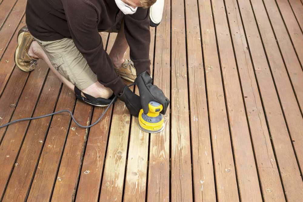 Man finishing deck with a palm sander